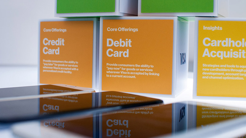 Three colored cubes at the Visa Innovation Center in Miami each with terms written on them, including credit card, debit card, and cardholder acquisition.