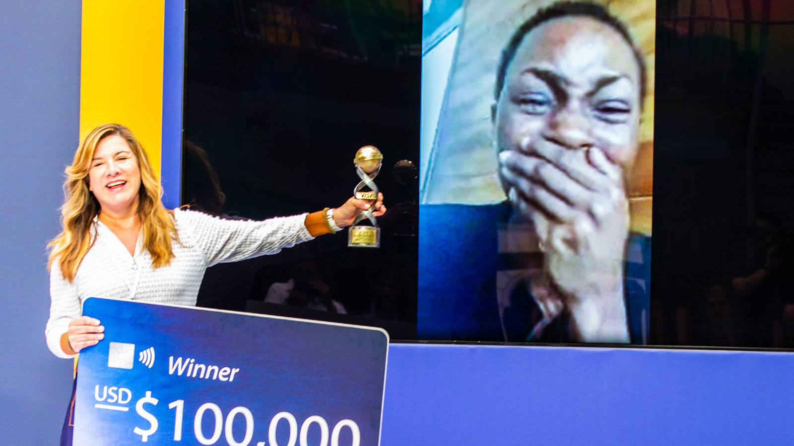 Woman presenting Monique Ntumngia, winner of the Social Impact challenge, a cutout of a Visa card worth $100k and a trophy.
